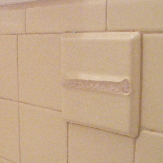 bathroom with broken ceramic tile toothbrush holder that has matching soap holder