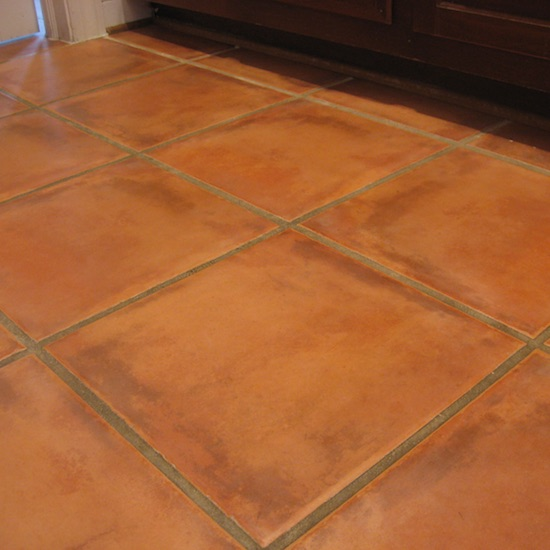 Terracotta tile floor with dirty grout that has lost seal